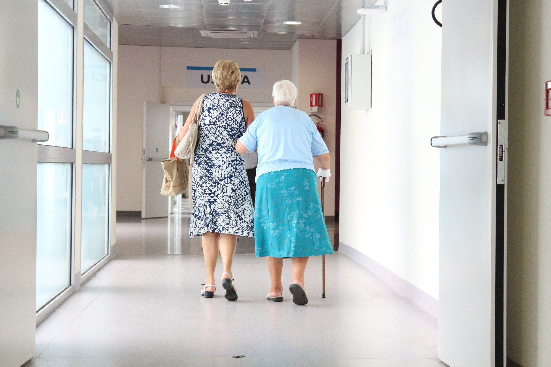 Woman and elderly mother in hospital hallway.