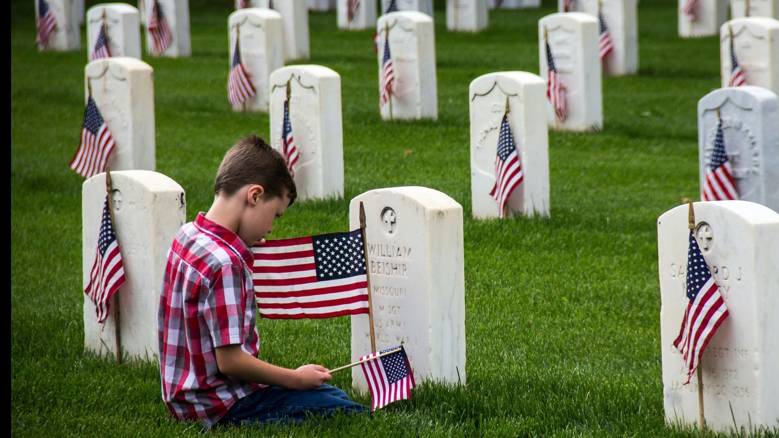 boy in red and white plaid shirt sitting on green grass with flags in front of military tombstone